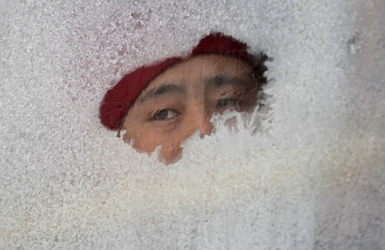 A woman looks out from a window of a bus covered with frost in Changchun, Jilin province December 16, 2014. Local temperatures in Changchun reached minus 21 degrees Celcius (minus 5.8 degrees Fahrenheit) on Tuesday, local media reported. Picture taken December 16. REUTERS/Stringer
