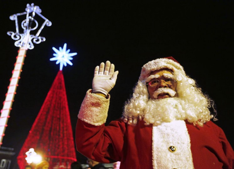 A man dressed as Santa Claus waves in front of an illuminated Christmas tree in Bogota on Little Candles' Day December 7, 2014. The traditional holiday, celebrated on December 7 in Colombia, marks the unofficial start of Christmas in the country. (John Vizcaino/Reuters)