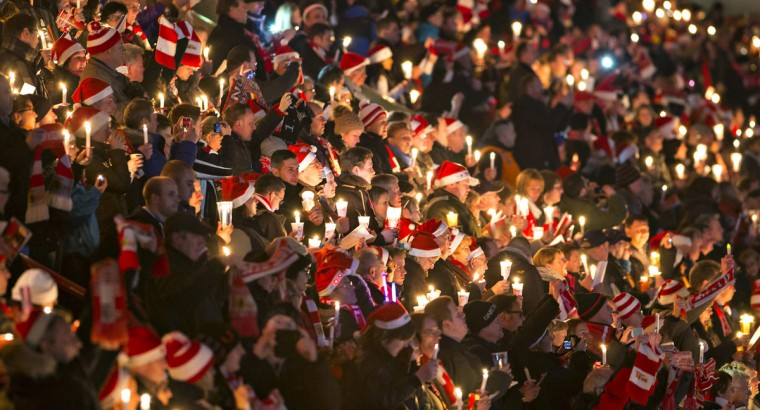 People attend the 'Weihnachtssingen' a candle-lit carol concert with 27,500 fans of the second-division club FC Union Berlin at the Alte Foersterei stadium in Berlin December 23, 2014. (REUTERS/Hannibal Hanschke)