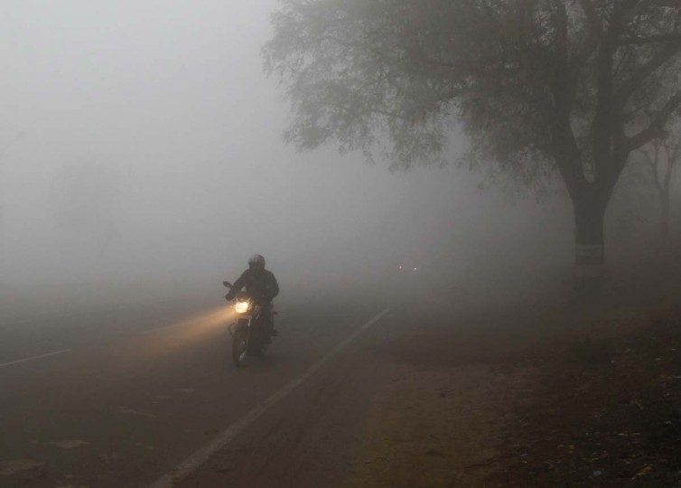 A man rides a motorcycle through dense fog on a road during winter morning in the northern Indian city of Allahabad December 19.  || PHOTO CREDIT: JITENDRA PRAKASH  - REUTERS