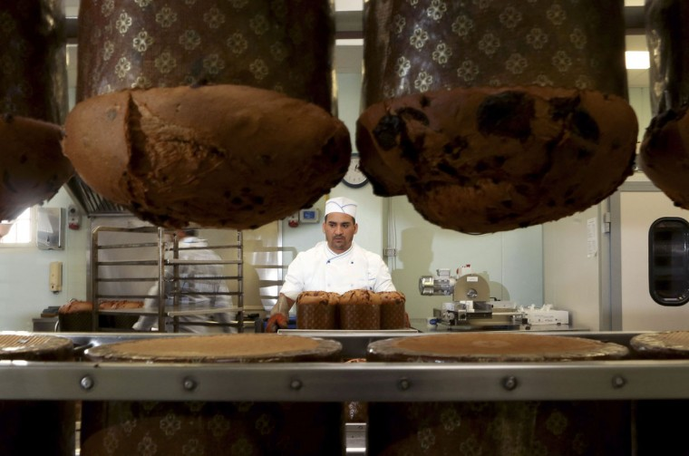 A prison baker prepares panettone cakes at Pasticceria Giotto in Padua's Due Palazzi prison. White-coated bakers are chopping nuts, dipping pastry into liquid chocolate and hanging freshly baked panettone Christmas cake upside down to preserve its domed shape. But when one of the all-male team steps outside to smoke, he is in a barred enclosure attached to Padua prison. Sweet smells have wafted through this building since 2005, when the local Giotto cooperative opened the 'Pasticceria Giotto', which they say is Italy's only bakery inside a jail. (Alessandro Bianchi/Reuters)