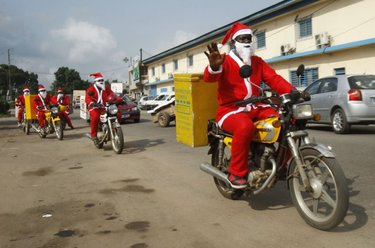 Jumia delivery men dressed as Santa Claus drive their motorcycles to deliver goods to customers in Abidjan December 18, 2014. Jumia is an African online retailer which offers goods ranging from electronics to kids' items. (Luc Gnago/Reuters)