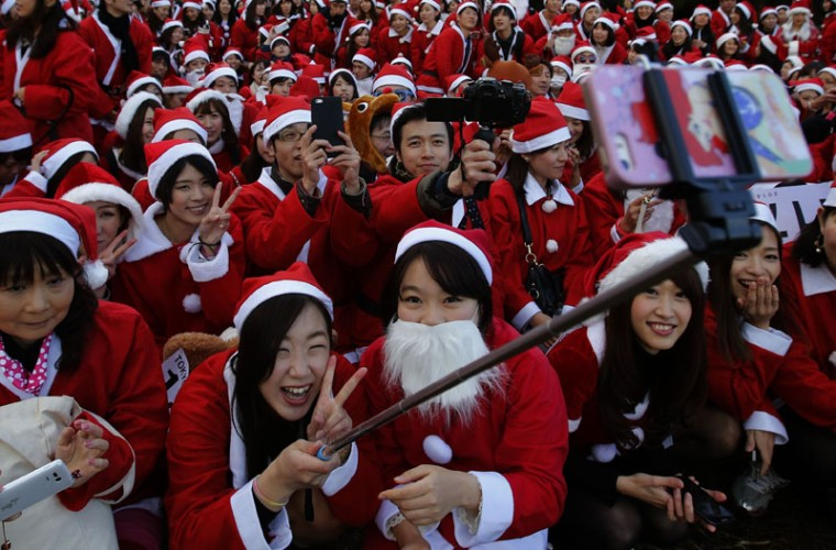 "People dressed in Santa costumes take ""selfies"" during the Tokyo Santa Run at a park in Tokyo December 6, 2014. Hundreds of people wearing costumes participated in the 2.5km (1.5 miles) charity run on Saturday to raise funds for children ahead of the upcoming Christmas season. (Yuya Shino/Reuters)"