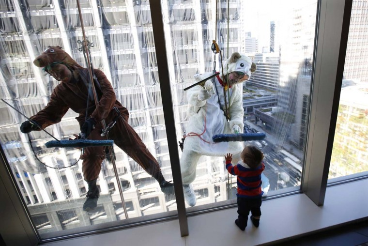 Window cleaners, dressed in horse and sheep costumes featuring animal signs from the Chinese zodiac calendar, work during an event promoting the year-end and new year at a hotel in the business district of Tokyo December 19. The year of 2014 is the year of the horse and 2015 is the year of the sheep according to the Chinese zodiac calendar.   || PHOTO CREDIT: ISSEI KATO  - REUTERS