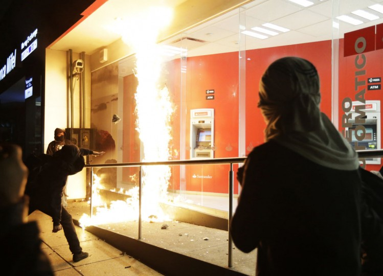 A demonstrator throws a firebomb at the windows of an ATM facility during a protest in support of the 43 missing trainee teachers in Mexico City December 1, 2014. The popularity of Mexican President Enrique Pena Nieto has sunk amid concerns about his handling of security problems and corruption, polls showed on Monday, in a sign that his ruling party could lose ground in elections next year. Polls noted the sharp drop in his approval rating since the apparent massacre of 43 trainee teachers students and a conflict of interest scandal involving a home being purchased by the first lady. (REUTERS/Tomas Bravo)