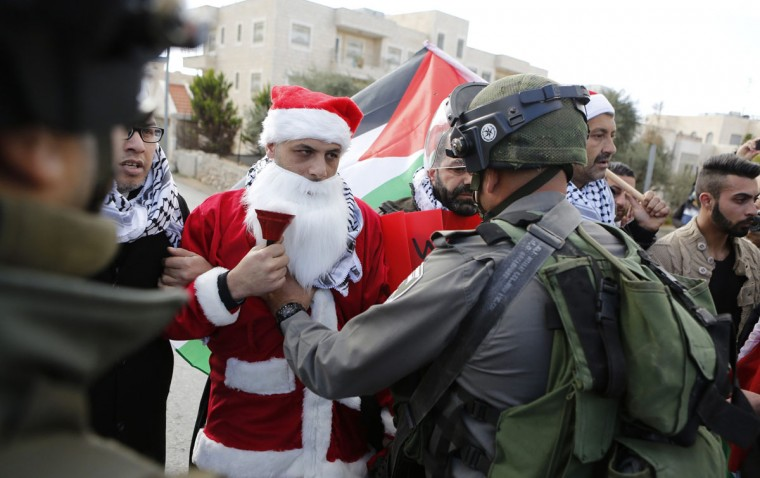 A Palestinian protester dressed in a Santa Claus costume argues with an Israeli border policeman during a demonstration against the Israeli settlements and demanding for free movement for the Palestinians during Christmas near a checkpoint in the West Bank city of Bethlehem December 23, 2014. (REUTERS/ Mussa Qawasma)