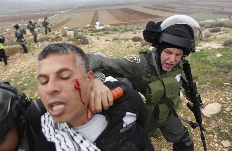 An Israeli border policeman detains a Palestinian protester during clashes following a demonstration against Israeli settlements in the West Bank village of Turmus Aya , near Ramallah  December 19.  || PHOTO CREDIT: MOHAMAD TOROKMAN  - REUTERS