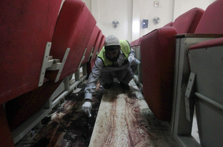 A policeman collects blood samples as evidence on the auditorium floor at the Army Public School, which was attacked by Pakistan Taliban gunmen, in Peshawar December 18, 2014. Pakistan on Wednesday began burying 132 students killed in a grisly attack on their school by Taliban militants that has heaped pressure on the government to do more to tackle an increasingly aggressive Taliban insurgency. REUTERS/Fayaz Aziz