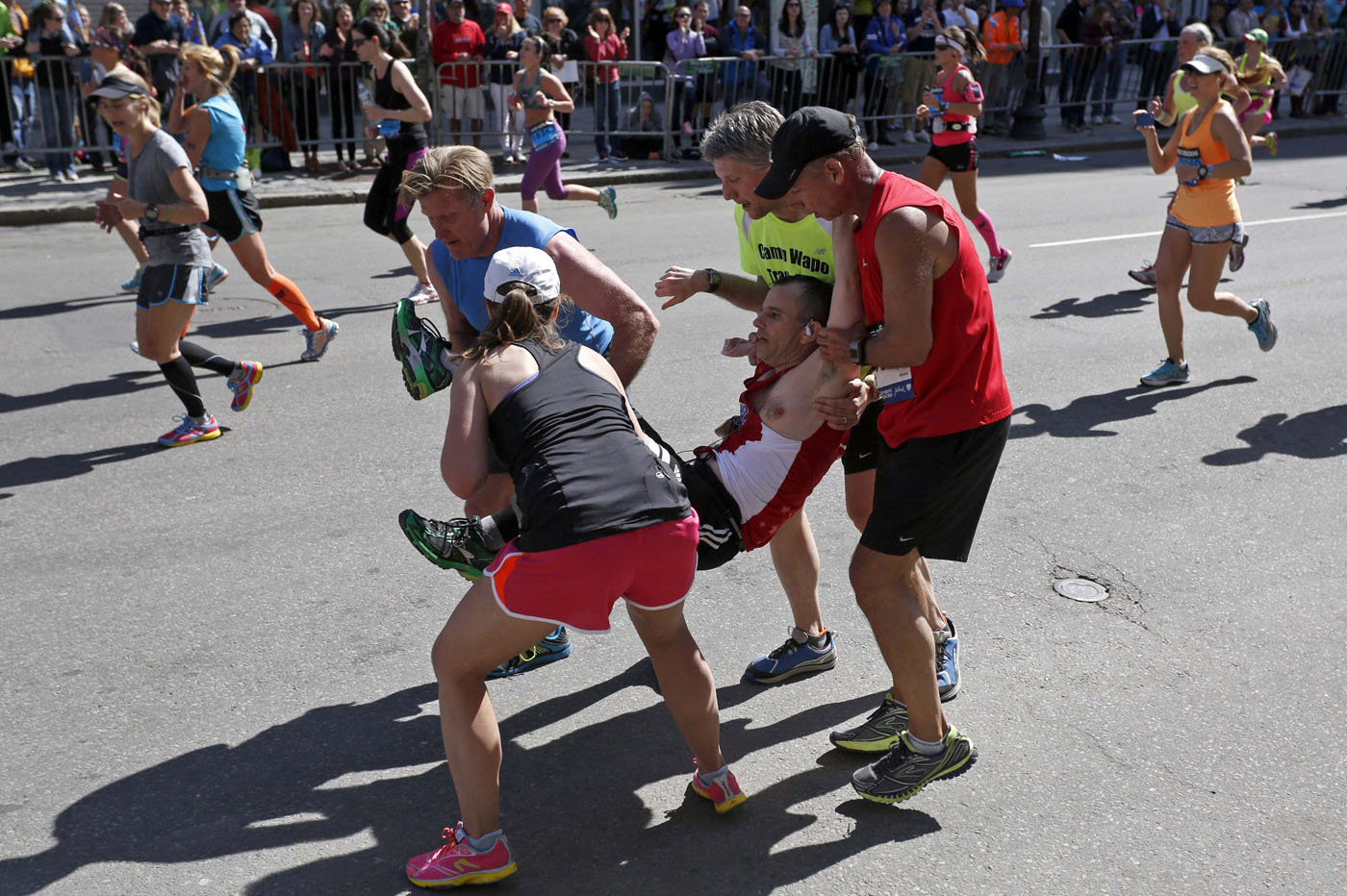 Four Runners Carry Adam Hurst Down Boylston Street After His Legs Locked Up During The 118th Running Of Boston Marathon In Massachusetts This