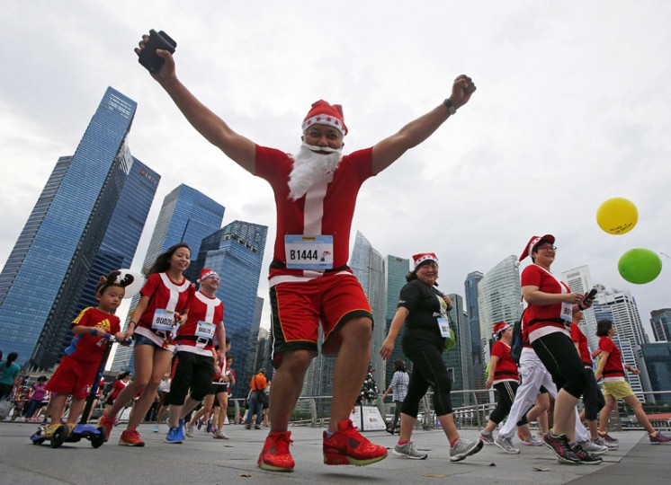 A participant reacts to the camera as they start the Santa Run for Wishes charity run along the Marina Promenade in Singapore's central business district November 29, 2014. The five kilometer fun run where participants dress up for the festive season aims to raise funds to grant wishes for children with life-threatening medical conditions between the ages of three to 18. (Edgar Su/Reuters)