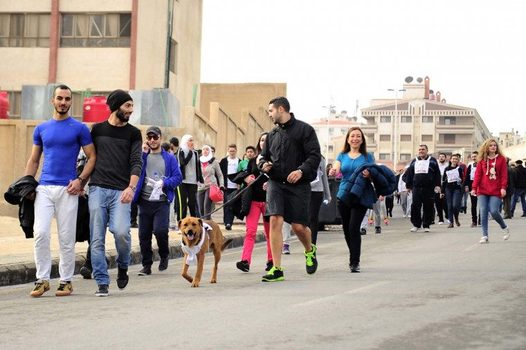 A man walks a dog as he joins others at a charity run organized by BASMA to raise funds for the treatment of children with cancer in Syria, at Dummar, west of Damascus December 19.    REUTERS/Omar Sanadiki