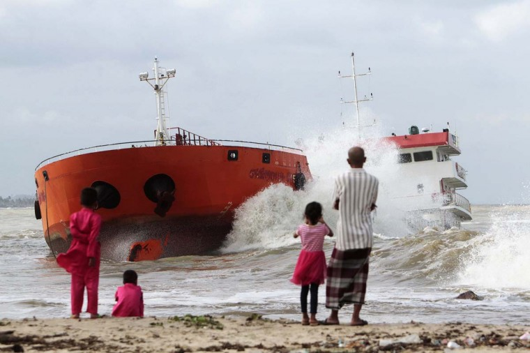 Locals watch from the beach as waves hit an Indonesian tanker that ran aground near Narathiwat in southern Thailand December 19. The tanker loaded with palm oil, previously hijacked by its crew members and then seized by Thai authorities, was anchored some 400 meters from the beach but strong wind and waves broke it free, according to local media.  || PHOTO CREDIT: SURAPAN BOONTHANOM  - REUTERS