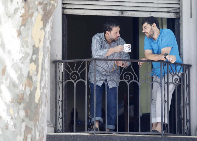 """Former Guantanamo detainees Adel bin Muhammad El Ouerghi (L) from Tunisia and Omar Mahmoud Faraj from Syria talk on a balcony in a neighbourhood in Montevideo December 12. Six former Guantanamo detainees were flown to Uruguay for resettlement on Sunday, the latest step in a slow-moving push by U.S. President Barack Obama to close the widely-condemned prison where most detainees have never been charged or tried. The men were discharged Thursday from a hospital in Montevideo and transferred to a house provided by Uruguay's central workers union Pit-Cnt. Uruguay will treat the six detainees it has taken in from the U.S. camp holding suspected terrorists in Guantanamo Bay as """"totally free men"""" who do not represent any security threat, the defence minister told Reuters on Monday. 