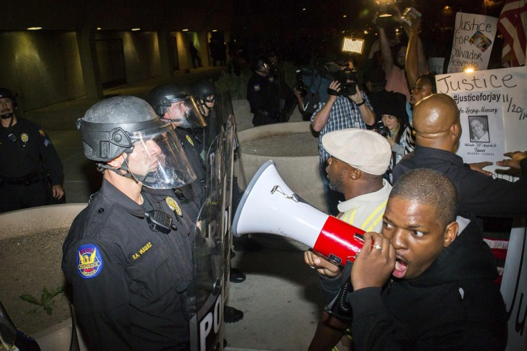 Protesters confront police outside the Phoenix Police Department the week after an unarmed man was shot dead by police, in Phoenix, Arizona December 8, 2014. Police say Rumain Brisbon, 34, was killed on December 2 as he struggled with a policeman who suspected he was selling drugs and erroneously believed he felt the handle of a gun in the man's pocket. Brisbon was actually carrying a pill bottle, and an attorney for his mother said accounts from witnesses did not tally with the police version. (Deanna Dent/Reuters)