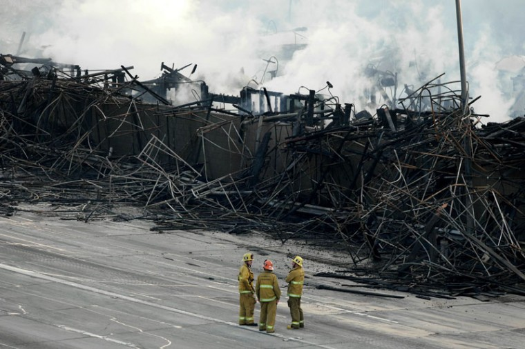 Firefighters stand on lanes of the 110 freeway near smoldering hot spots of a large fire that consumed an apartment building that was under construction in Los Angeles, California December 8, 2014. The blaze in downtown Los Angeles early on Monday shut down two major freeways, the Los Angeles Fire Department and California Highway Patrol said. The fire was extinguished, but firefighters were still on the scene monitoring hot spots. There were no reports of injuries or fatalities in the fire. (Jonathan Alcorn/Reuters)