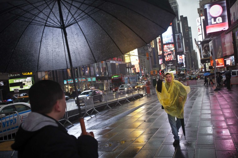A man in a rain poncho takes a photo of his friend under the pouring rain in Times Square, New York December 9, 2014. (Carlo Allegri/Reuters)