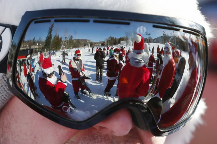 Skiers and snowboarders dressed as Santa Claus are reflected in a skier's goggles before participating in a charity run down a slope at Sunday River Ski Resort in Newry, Maine December 7, 2014. Organizers say 250 skiing Santas raised $2700 for charity at the event. (Brian Snyder/Reuters)