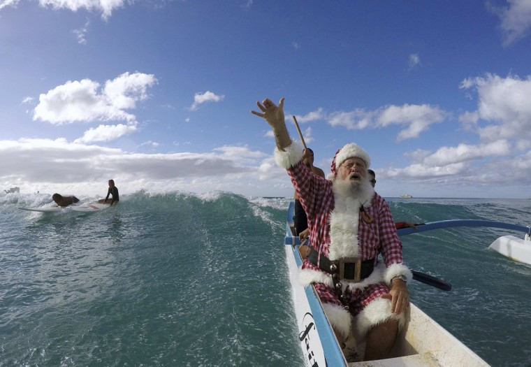 Donald Boyce, dressed up like Santa Claus, waves to surfers as he goes outrigger canoe surfing off Waikiki beach in Honolulu, Hawaii December 13, 2014. (Hugh Gentry/Reuters)