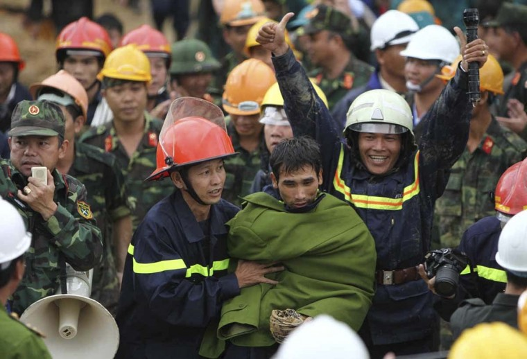 Rescuers walk next to a worker after freeing him and others from a collapsed tunnel at a construction site of a hydropower plant in Vietnam's central province of Lam Dong December 19. Vietnamese rescuers on Friday saved 12 workers trapped in the tunnel that collapsed during construction of the hydropower plant after nearly four days of digging, drilling and hoping. Mandatory credit.   || PHOTO CREDIT: DUONG GIANG/VNA  - REUTERS