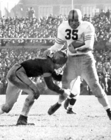 Clyde Scott (47) was the offensive and defensive star for Navy. Army's Felix (Doc) Blanchard (35) started off on one of his power drives through the line, but when he hit Scott, Doc was stopped cold. Army won, 23-7. (UM Libraries, Special Collections, News American Photo)