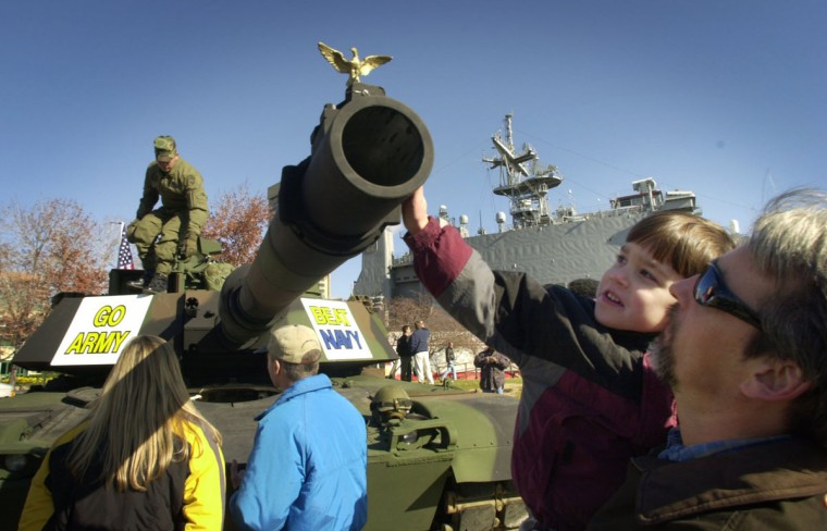 Carney resident Gary Ropka holds his son Bradley Ropka, 4, as he touches the 120mm barrel of a M1A2 Abrams tank on display at the Inner Harbor in preparation for the Army -Navy football game on Saturday. (Baltimore Sun photo by John Makely)