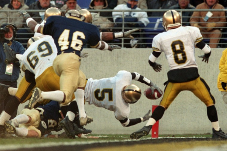A pile of bodies follows Army defensive back Ben Woodruff (5) who breaks the goal line for a touchdown following a blocked punt in the third quarter at PSINet Stadium on Dec. 2, 2000. The Midshipmen turned back the Black Knights, 30-28. (Baltimore Sun/Karl Merton Ferron)