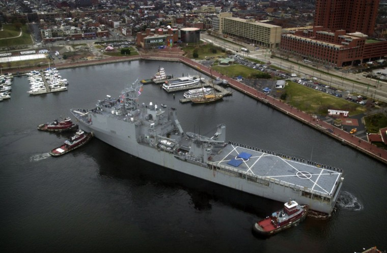 The U.S.S. Carter Hall, an amphibious Landing Ship Dock, is helped by three tug boats as it docks on the west wall of the Inner Harbor. The 609-foot ship, whose home port is Virginia Beach, visited Baltimore to help celebrate the Army-Navy football game at PSINet Stadium. (Baltimore Sun/Karl Merton Ferron)