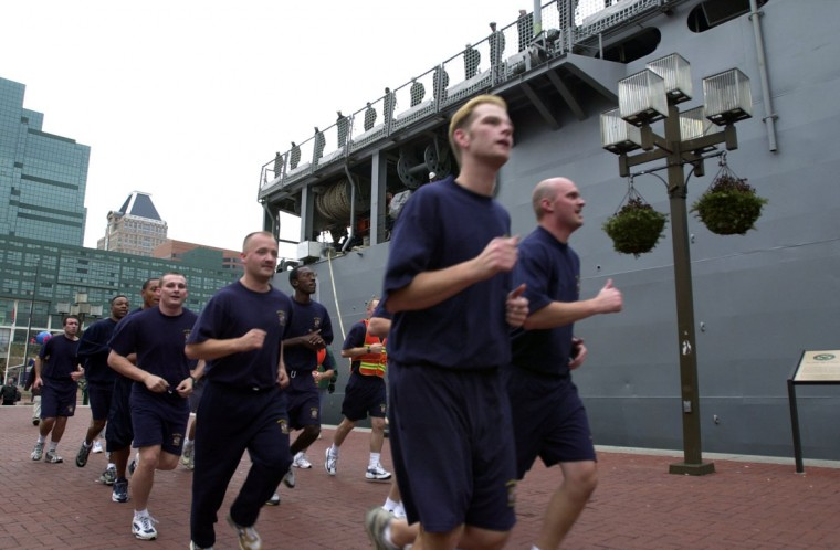 Baltimore City Police cadets jog beneath the U.S.S. Carter Hall, a 609-foot ship docked at the Inner Harbor to help celebrate the Army-Navy football game at PSINet Stadium. (Baltimore Sun/Karl Merton Ferron)