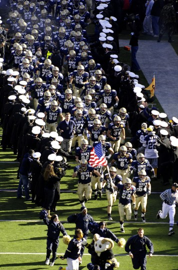 The Navy football team runs onto the field prior to the start of the 108th annual Army-Navy football game at M&T Bank Stadium on Dec. 1, 2007. (AP Photo/Gail Burton)