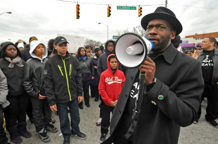Pastor Jamal Bryant addresses the protesters before they lay down in the intersection on Reisterstown Road near Reisterstown Road Plaza. (Amy Davis / Baltimore Sun)