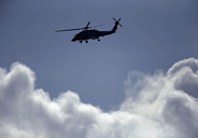 A U.S. Coast Guard helicopter makes its way past storm clouds as it patrols the coastline near Solana Beach, California December 12, 2014. (Mike Blake/Reuters photo)