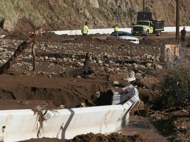 A work crew approaches a car stuck in mud on Pacific Coast Highway in Malibu, California December 12, 2014. A Pacific storm pounded Southern California with heavy rain and high winds on Friday, triggering flash floods and mudslides that prompted the evacuation of hundreds of homes, damaged dozens of others and disrupted passenger rail service along the coast. (Jonathan Alcorn/Reuters photo)