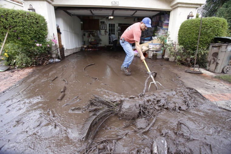 Salvador Medina cleans the garage of homeowner Durston Williams on Irena Avenue located near homes buried by the debris flow on Dec. 12, 2014 in Camarillo Springs, Calif. (Al Seib/Los Angeles Times)