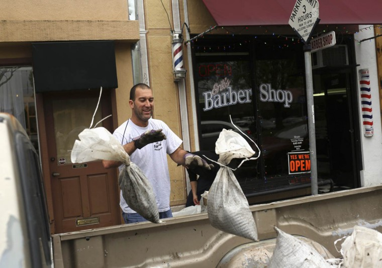 Randy Parmeter throws sand bags used to protect a barber shop from floodwaters into the bed of a pickup truck in Healdsburg, California December 12, 2014. Businesses and residents were cleaning up after a storm dropped heavy rainfall on the area 80 miles north of San Francisco. (Robert Galbraith/Reuters photo)