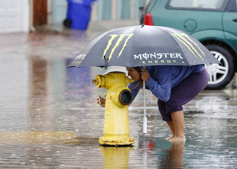 A woman takes a picture with her phone along a street in Mission Beach as a winter storm brings rain and high winds to San Diego, California December 12, 2014. (Mike Blake/Reuters photo)