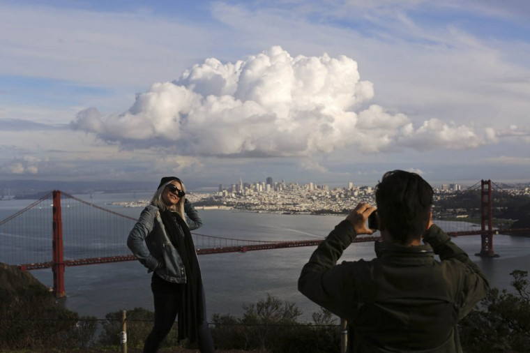 Visitors to the Marin Headlands pose for photographs overlooking the Golden Gate Bridge and skyline of San Francisco, as a large cloud gathers over the city, December 12, 2014. A major storm pummeled California and the Pacific Northwest with heavy rain and high winds on Thursday, killing one man, knocking out power to tens of thousands of homes, disrupting flights and prompting schools to close. (Robert Galbraith/Reuters photo)