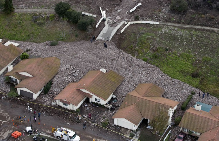 A group of houses are pictured after boulder-strewn rivers of mud swept down hillsides during a winter storm, in Camarillo Springs, California December 12, 2014. A Pacific storm pounded Southern California with heavy rain and high winds on Friday, triggering flash floods and mudslides that prompted the evacuation of hundreds of homes, damaged dozens of others and disrupted passenger rail service along the coast. One of the areas hardest hit on Friday was the community of Camarillo Springs, north of Los Angeles. (Mario Anzuoni/Reuters photo)