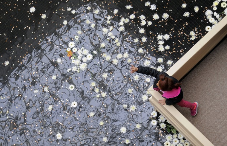 White flowers are tossed into a fountain at The Mall in Columbia a week after the mall shooting of Zumiez employees Brianna Benlolo and Tyler Johnson. (Kim Hairston/Baltimore Sun Staff.)