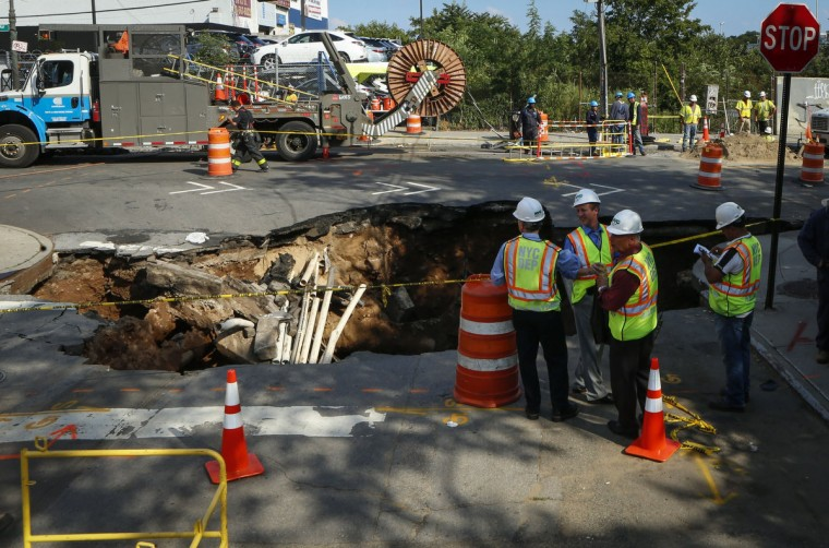 New York City firefighters work at the scene where a sinkhole opened up in Brooklyn, New York on August 4, 2015.  New Yorkers living in the borough of Brooklyn woke to a strange sight on Tuesday -- a giant sinkhole had swallowed an enormous chunk of road. The sinkhole, formed by the natural process of erosion, appeared early in the morning at an intersection in the neighborhood of Sunset Park, according to the Fire Department. The gaping hole exposed torn pipes and crushed asphalt at the intersection of Fifth Avenue and 64th Street. No one was hurt.  (Kena Betancur/AFP/Getty Images)
