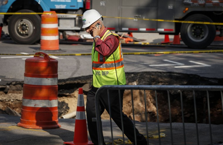 A worker of New York City Department of Environmental Protection attends an emergency where a giant sinkhole opened up at Sunset Park in   Brooklyn, New York on August 04, 2015. (Kena Betancur/AFP/Getty Images)