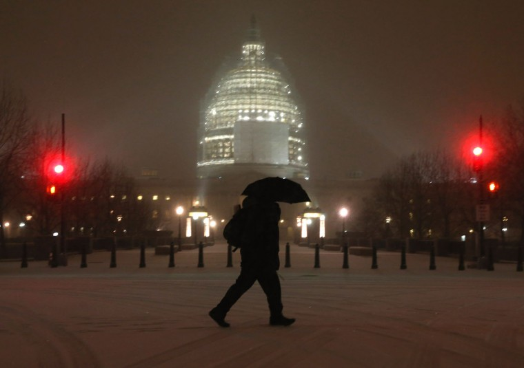 A man walks through falling snow in front of the US Capitol , January 6, 2015 in Washington, DC. Later today Congress will convene its first session of the 114th Congress with Republicans controlling both the House and Senate. (Photo by Mark Wilson/Getty Images)