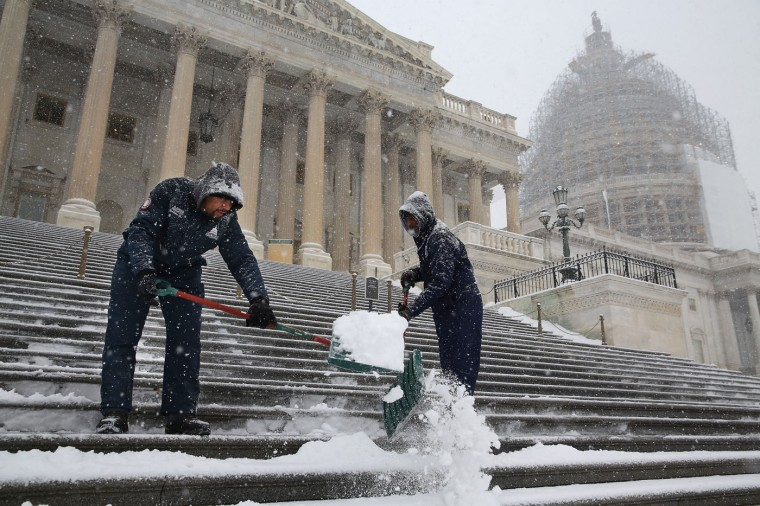 Clearing a path for the new Congress, employees of the Architect of the Capitol shovel snow off the steps of the U.S. House of Representatives as more snow continues to fall January 6, 2015 in Washington, DC. Tuesday is the opening day of the 114th Congress. (Photo by Chip Somodevilla/Getty Images)