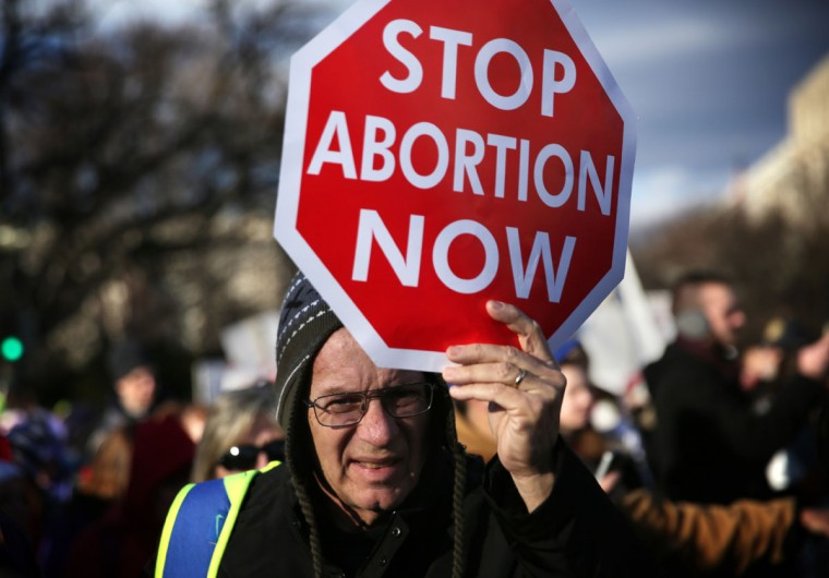 A pro-life activist holds a sign as he participates in the annual March for Life January 22, 2015 in Washington, DC. (Photo by Alex Wong/Getty Images)