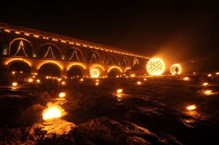 People gather in front of the Pont du Gard decorated with lights during the 'Nuit des Lucioles', an event to celebrate the 30th anniversary of the Roman aqueduct registration as a UNESCO World Heritage Site on January 8, 2015 in Vers-Pont-du-Gard, southern France.  || CREDIT: SYLVAIN THOMAS - AFP/GETTY IMAGES