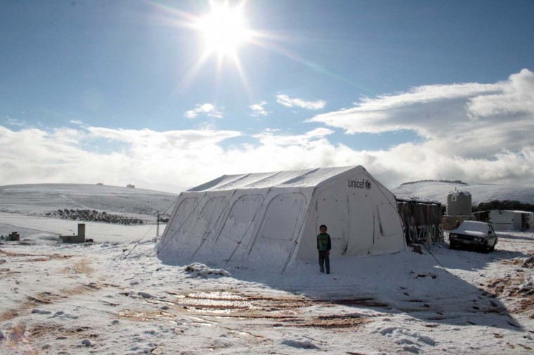 A child stands outside a tent on January 9 at a Syrian refugee camp covered with snow in Marj al-Khawkh, on the outskirts of the southern Lebanese town of Marjayoun. Two Syrians, a man and a six-year-old boy, were found dead on January 7 in Ain al-Joz in the mountains by Shebaa, as a major storm hit the Middle East, bringing misery to thousands of Syrian refugees living in makeshift camps throughout Lebanon.  || CREDIT: ALI DIA - AFP/GETTY IMAGES
