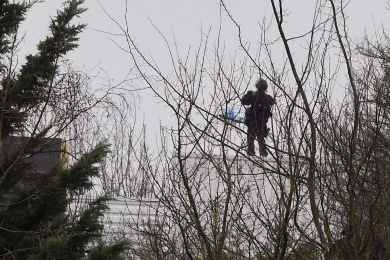 A French police officer stands on the roof of a building where two brothers suspected of slaughtering 12 people in an Islamist attack on French satirical newspaper Charlie Hebdo held one person hostage as police cornered the gunmen, in Dammartin-en-Goele, northeast of the capital, on January 9. The hostage drama unfolded at a printing business in the small town of Dammartin-en-Goele, only 12 kilometres (seven miles) from Paris's main Charles de Gaulle airport, police sources said.  || CREDIT: DOMINIQUE FAGET - AFP/GETTY IMAGES