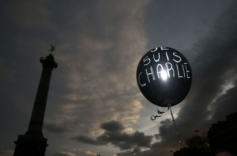 """A balloon reading """"Je suis Charlie"""" (I am Charlie) is held at Place de la Bastille during the Unity rally """"Marche Republicaine"""" on January 11, 2015 in Paris in tribute to the 17 victims of a three-day killing spree by homegrown Islamists. The killings began on January 7 with an assault on the Charlie Hebdo satirical magazine in Paris that saw two brothers massacre 12 people including some of the country's best-known cartoonists, the killing of a policewoman and the storming of a Jewish supermarket on the eastern fringes of the capital which killed 4 local residents. (Joel Saget/AFP/Getty Images)"""