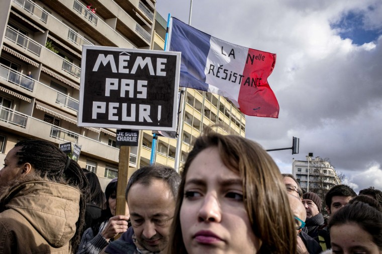 """People hold a placard reading """"Not even afraid"""" and a French flag reading """"The new resistance"""" take part in a Unity rally Marche Republicaine on January 11, 2015 in Lyon in tribute to the 17 victims of the three-day killing spree. The killings began on January 7 with an assault on the Charlie Hebdo satirical magazine in Paris that saw two brothers massacre 12 people including some of the country's best-known cartoonists and the storming of a Jewish supermarket on the eastern fringes of the capital which killed 4 local residents. (Jeff Pachoud/AFP/Getty Images)"""
