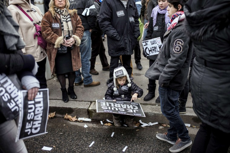 """A child holds a placard reading """"Je suis Charlie"""" (I am Charlie) during a Unity rally Marche Republicaine on January 11, 2015 in Lyon in tribute to the 17 victims of the three-day killing spree. The killings began on January 7 with an assault on the Charlie Hebdo satirical magazine in Paris that saw two brothers massacre 12 people including some of the country's best-known cartoonists and the storming of a Jewish supermarket on the eastern fringes of the capital which killed 4 local residents. (Jeff Pachoud/AFP/Getty Images)"""