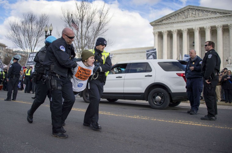 A pro-choice activist is arrested and carried away by US Capitol police after blocking the road against the March For Life's path in front of the US Supreme Court in Washington, DC, January 22, 2015. (JIM WATSON/AFP/Getty Images)